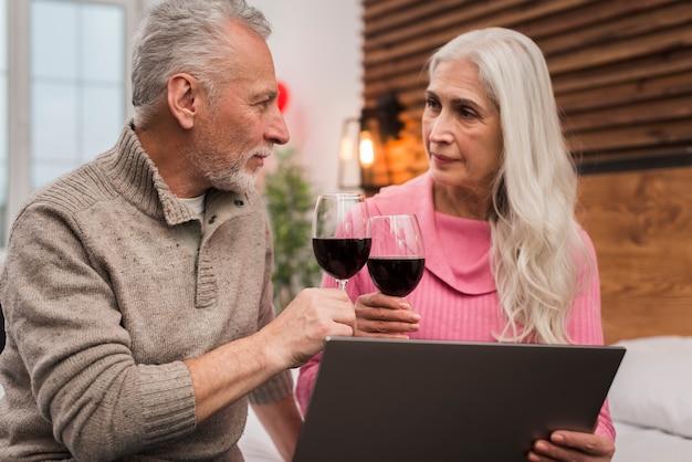 Пожилая пара пьет вино с макетом