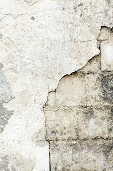 露出した汚れたレンガのセメント壁