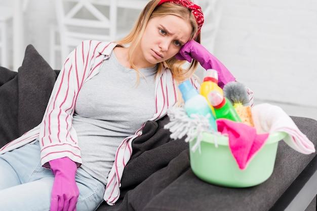 Женщина высокого угла с чистящими средствами