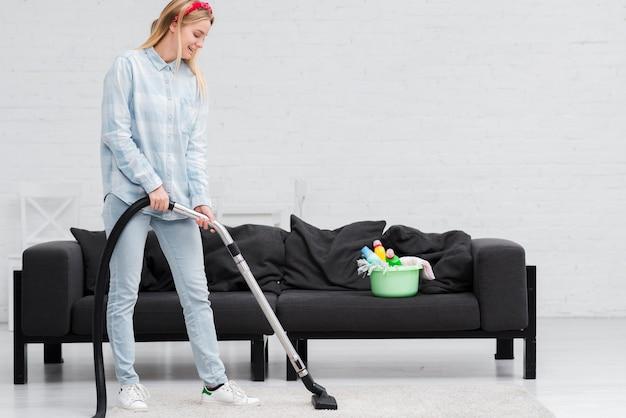 自宅で掃除機を持つ女性