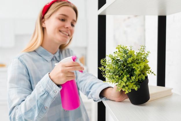 Женщина опрыскивает растение у себя дома