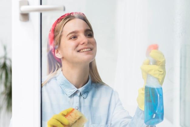 Молодая женщина, мытье окон