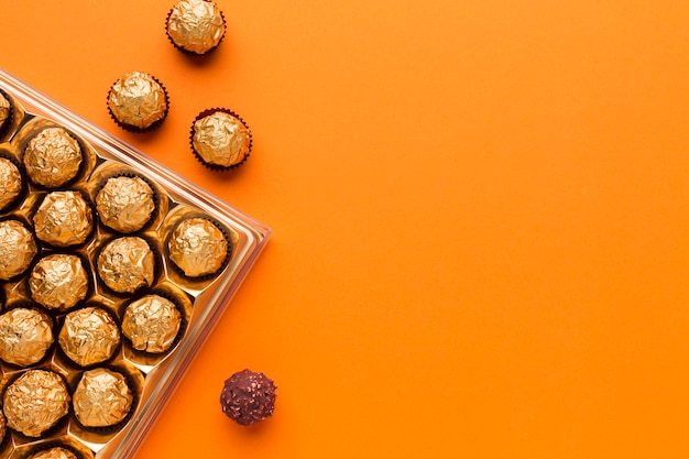 オレンジ色のテーブルの上のトップビューおいしいチョコレート