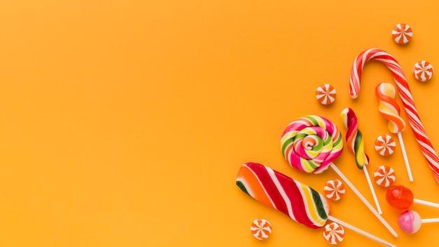 コピースペースを持つオレンジ色のテーブルに美味しいお菓子