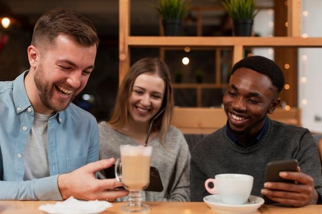 Юные друзья смотрят на телефоны