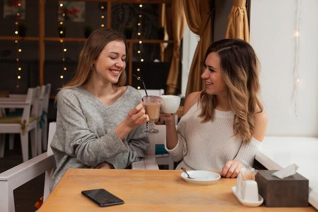 Улыбающиеся подруги пьют кофе