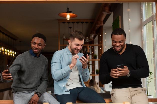 Молодые мужчины смотрят на мобильные телефоны
