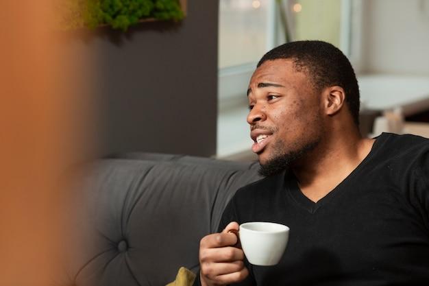 Улыбающийся молодой человек пьет кофе