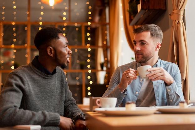 Друзья-мужчины разговаривают за чашкой кофе
