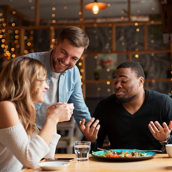 Улыбающиеся друзья в ресторане вместе