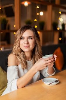 Красивая женщина пьет чашку кофе