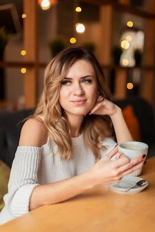 Молодая женщина пьет кофе