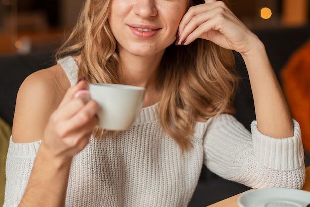 Крупным планом женщина пьет чашку кофе