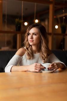 Низкий угол женщина пьет чашку кофе