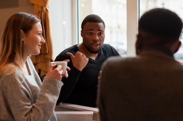 Группа друзей говорить и пить кофе