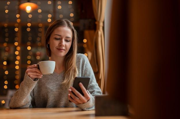 Портрет красивая женщина, глядя на мобильный