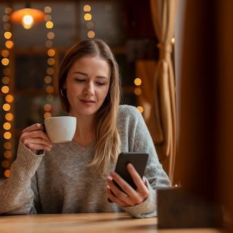 Портрет красивая женщина, глядя на телефон