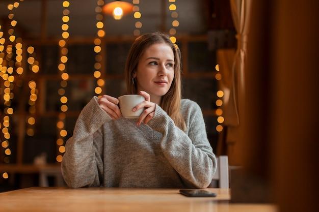 Низкий угол женщина пьет кофе