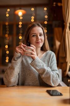 Улыбка женщины, наслаждаясь чашечкой кофе