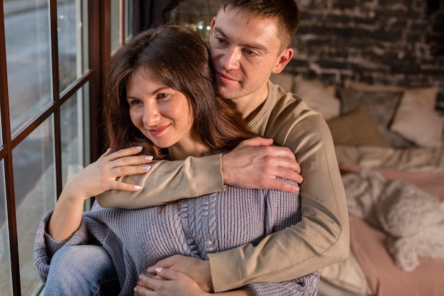 Романтическая пара обнимается и смотрит в окно