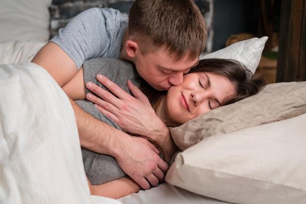 ベッドでガールフレンドにキスをする男性の側面図