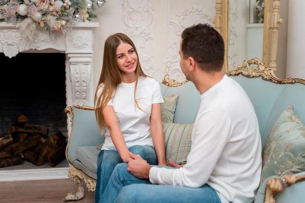 Счастливая пара, держась за руки на диване