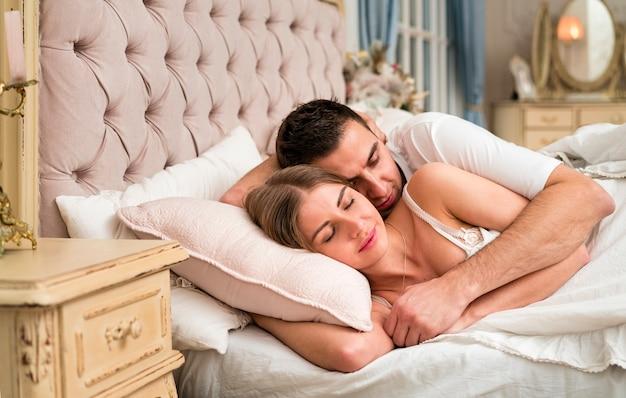 ベッドで寝ているカップルを採用
