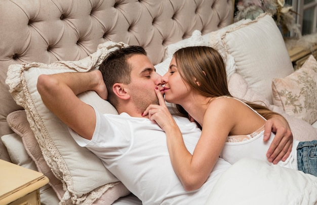 ロマンチックなカップルがベッドに抱きしめるキス