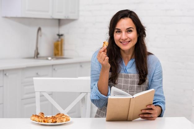 Молодая женщина читает книгу на кухне
