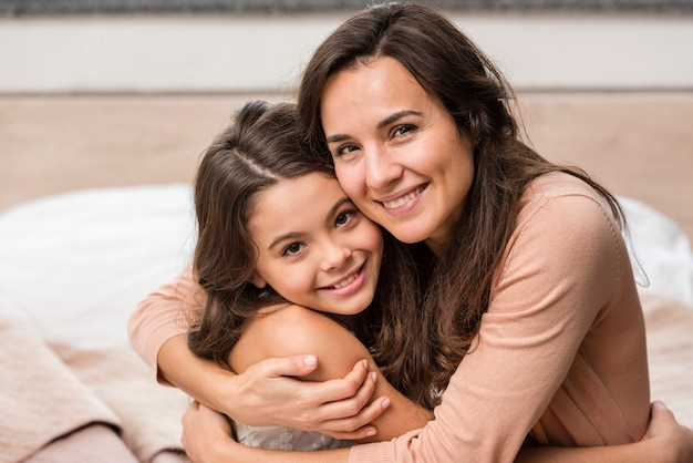 Мать и дочь обнимаются дома