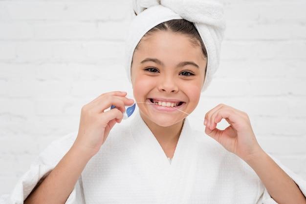 少女が彼女の歯をフロス