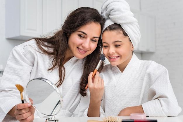娘と母親が化粧をしています