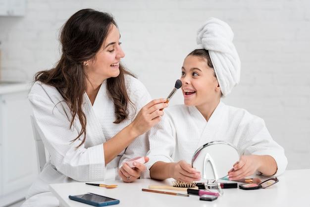 母と娘が一緒に化粧をしています