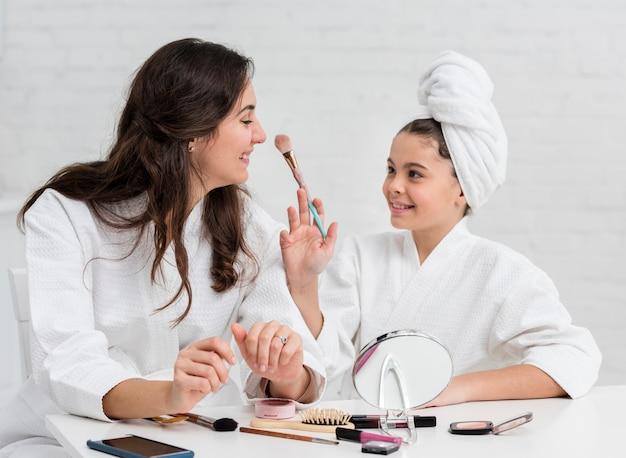 母と娘が化粧をしています