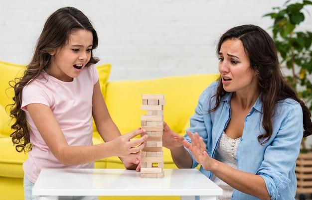 Мать играет с дочерью в настольную игру