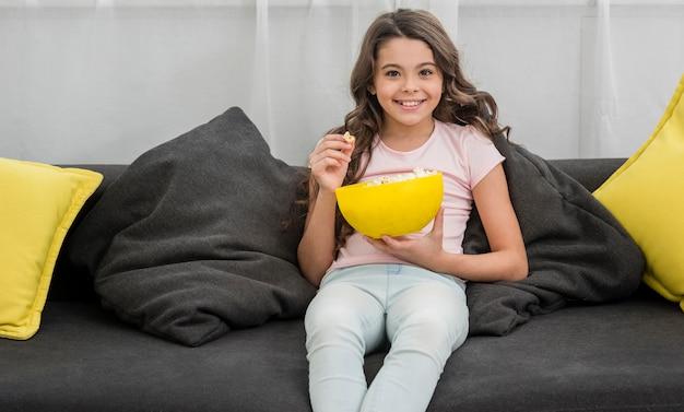 Маленькая девочка ест попкорн в гостиной