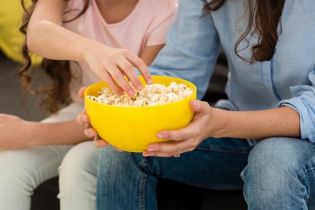 母と娘のポップコーンのクローズアップを食べる