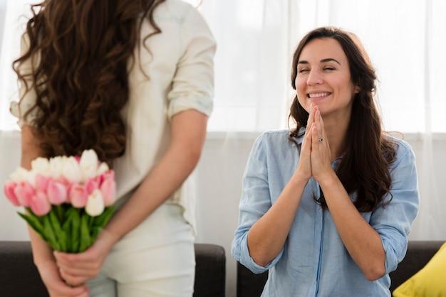 彼女の母親に花の花束を与える娘