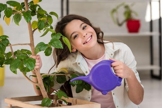 Милая маленькая девочка поливает растение