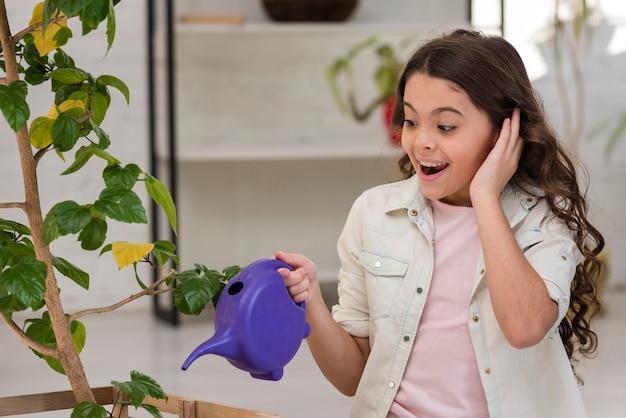 Маленькая девочка поливает растение