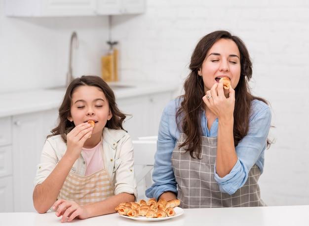 ママと娘が一緒にいくつかのペストリーを食べる