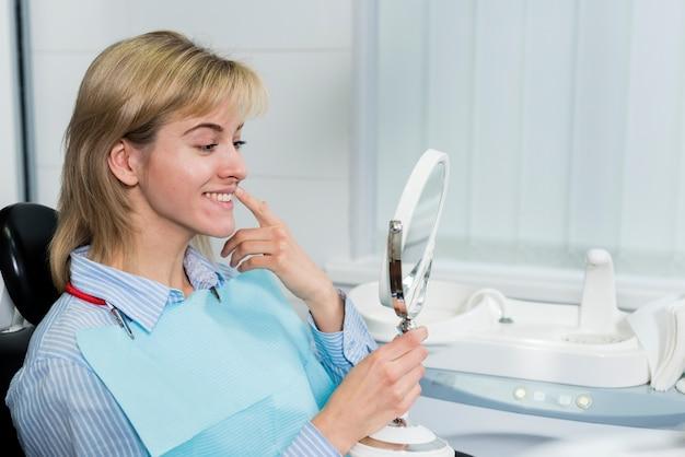 Молодая женщина, проверка ее зубы в зеркале