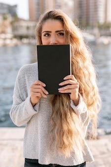 本で彼女の口を覆っている美しい若い女性