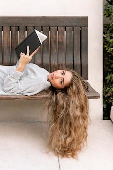 Красивая молодая женщина, держащая книгу на скамейке