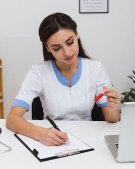 Красивый доктор пишет отчет и держит образец крови