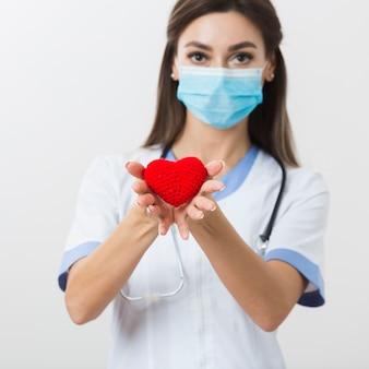 Женский доктор предлагая плюшевое сердце