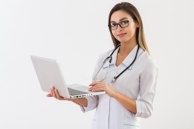 美しい医者はラップトップを保持しているとカメラマンを見て