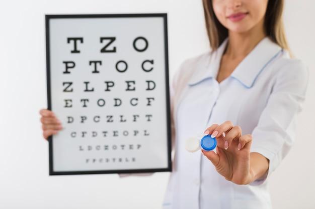 Женский доктор держа панель испытания глаза