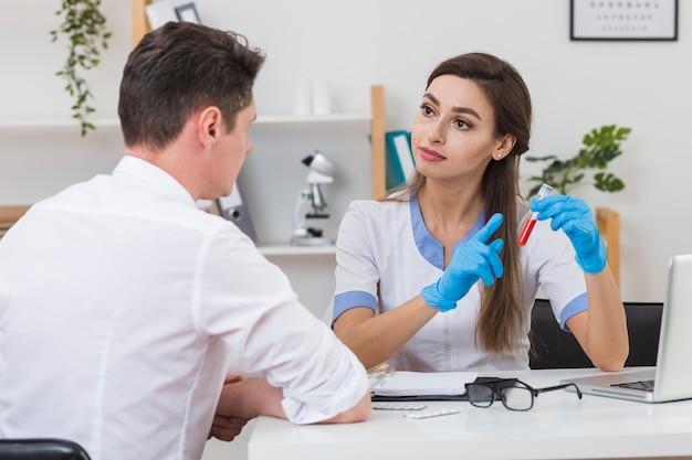 Красивый доктор показывая образец крови к пациенту
