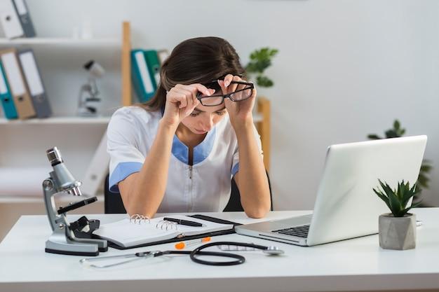 Усталая женщина-врач вынимает очки